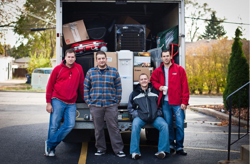 Four Devbridge employees in front of a packed moving truck